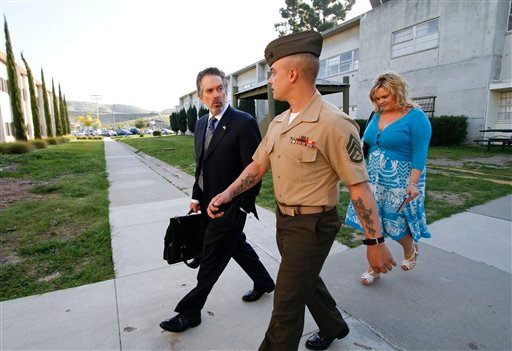Marine Corps Staff Sgt. Frank Wuterich, center, arrives for a pretrial hearing with attorney Neil Puckett, left, and friend, Melissa Balcombe, right. (AP Photo/Denis Poroy)