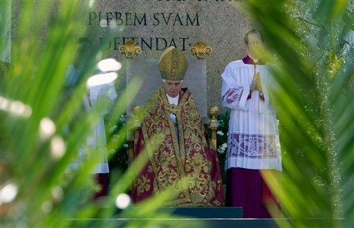 Pope Benedict XVI is framed by palm tree branches during an open-air Palm Sunday mass in St. Peter's square at the Vatican, Sunday, March 28, 2010. (AP Photo/Andrew Medichini)