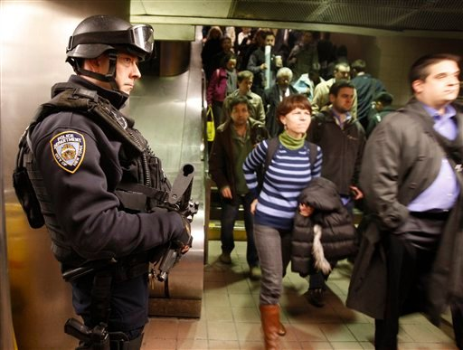 An NYPD counterterrorism officer watches commuters entering the subway at Grand Central Station in New York, Monday, March 29, 2010. (AP Photo/Kathy Willens)