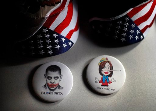 """Buttons depicting President Barack Obama and House Speaker Nancy Pelosi are shown at the site of the """"Showdown in Searchlight"""" tea party rally in Searchlight, Nev., Friday, March 26, 2010. (AP Photo/Jae C. Hong)"""