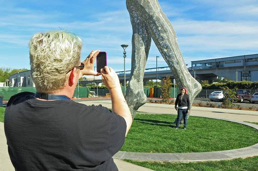 In this photo taken Wednesday Oct. 19, 2016, art teachers Jo Sutton, left, and Jennifer Jervis, right, take pictures beneath a 55-foot nude statue in San Leandro, Calif.