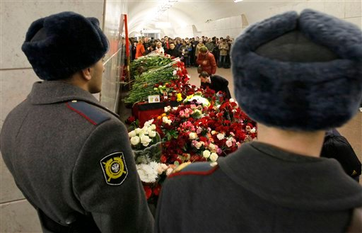 People place flowers at the sight of the explosion at Lubyanka subway station in Moscow, Russia, Tuesday, March 30, 2010. (AP Photo/Dmitry Lovetsky)