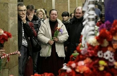 People stand at the sight of the explosion at Park Kultury subway station in Moscow, Russia, Tuesday, March 30, 2010. Flowers overflowed Tuesday from rickety tables in two Moscow subway stations in memory of the 39 passengers.