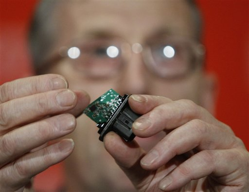 Dr. Anthony Anderson, an electrical failure expert, holds an electronic chip from an acceleration pedal assembly during a news conference at the National Press Club in Washington, Tuesday, March 23, 2010, to discuss Toyota's sudden acceleration problems.