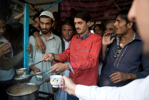 Pakistani tea vendor Arshad Khan, 18, center, prepares tea at a stall in a market in Islamabad, Pakistan, Friday, Oct. 21, 2016.
