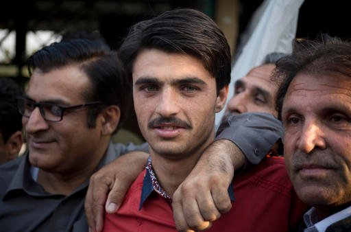 Pakistani tea vendor Arshad Khan, 18, center, is surrounded by shopkeepers and colleagues at a market where he sells tea in Islamabad, Pakistan, Friday, Oct. 21, 2016.