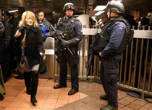 A woman walks past two heavily-armed counterterrorism officers stationed outside the turnstiles at Grand Central Station in New York, Monday, March 29, 2010.