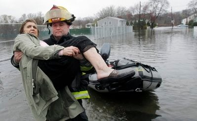 Lt. Brian Poland, of the East Providence, R.I., fire department, carries Phyllis Rego to dry land while helping rescue her from a flooded neighborhood in East Providence, Tuesday, March 30, 2010. (AP Photo/Charles Krupa)