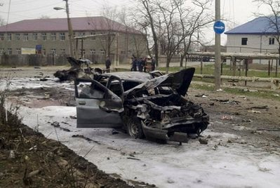 Cars damaged in an explosion are seen in Kizlyar, a town in the southern Russian region of Dagestan, Wednesday, March 31, 2010. Two suicide bombers including one impersonating a police officer killed and injured dozens of people.