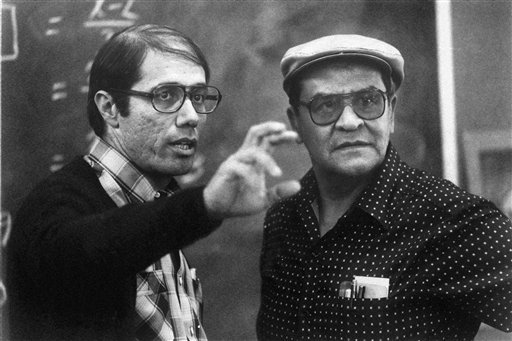 """This March 9, 1988 file provided by Warner Bros., shows actor Edward James Olmos, left, comparing notes with high school teacher Jaime Escalante during the filming of the Warner Bros. film """"Stand And Deliver,"""" in Los Angeles. (AP Photo/Warner Bros., File)"""