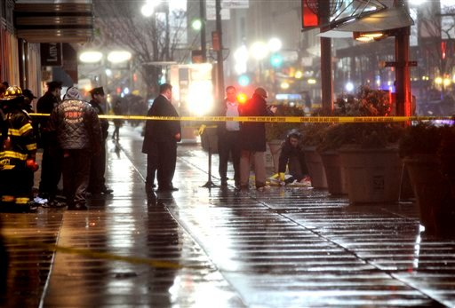 A medical examiner looks at the body of a man who plunged to his death from the 34th street side of the Empire State building, Tuesday, March 30, 2010, in New York.