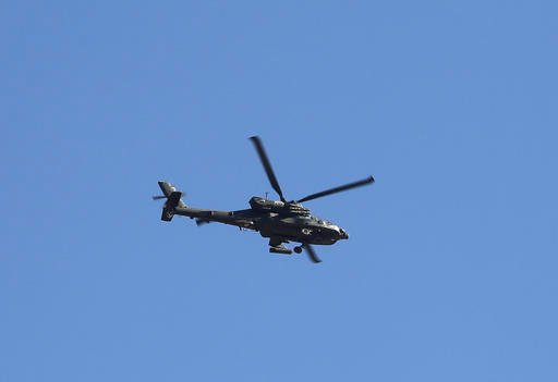(AP Photo/Khalid Mohammed). A helicopter of the U.S.-led coalition flies over the town of Bartella, Iraq, Saturday, Oct. 22, 2016. Iraqi forces retook Bartella, around 15 kilometers (9 miles) east of Mosul, earlier this week, but are still facing pocke...