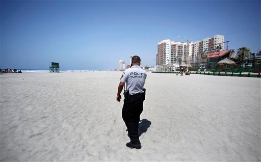In this March 30, 2009, file photo, Rosarito Beach tourist police officer Roberto Casas patrols a massive but empty beach during the middle of what was once a hectic spring break period in Playas de Rosarito, Mexico.