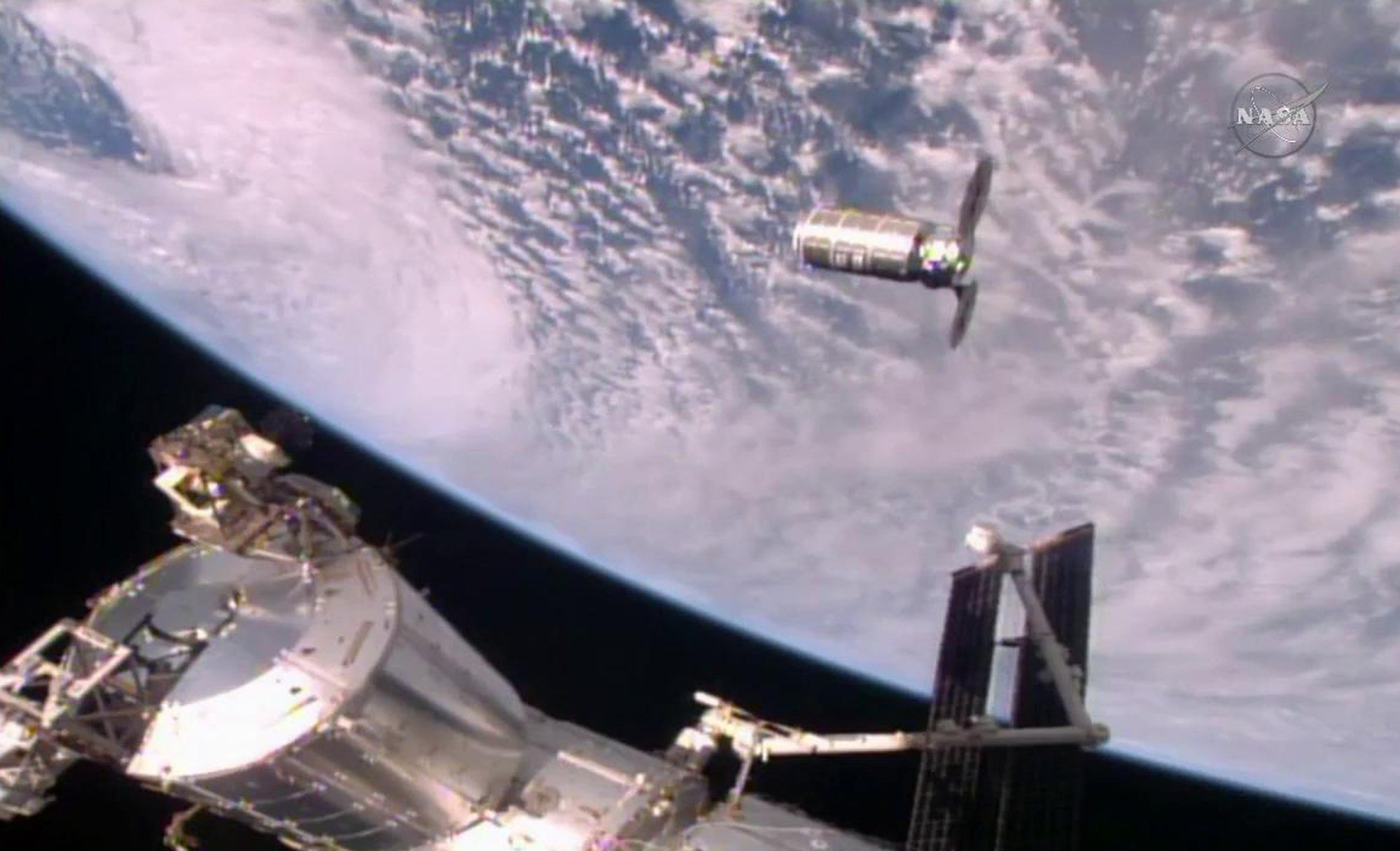 This photo provided by NASA TV shows the Cygnus resupply ship, above, slowly approaching the International Space Station before the Canadarm2 reaches out and grapples it, Sunday, Oct. 23, 2016. Once the Cygnus is unloaded, it will be filled with trash and