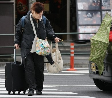 A woman tries to control her umbrella against strong winds as she crosses an intersection in central Tokyo on Friday, April 2, 2010.