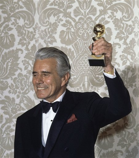 """In a Saturday, Jan. 30, 1983 photo, actor John Forsythe celebrates after accepting the Golden Globe Award for best actor in a dramatic television series, """"Dyanasty,"""" in Hollywood, Calif."""
