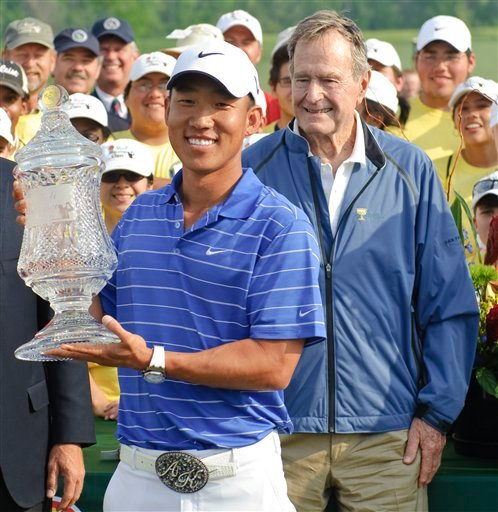 Anthony Kim holds the championship trophy as former President George H. W. Bush, right, watches after the final round of the Houston Open PGA Tour golf tournament Sunday, April 4, 2010 in Humble, Texas.  (AP Photo/Dave Einsel)
