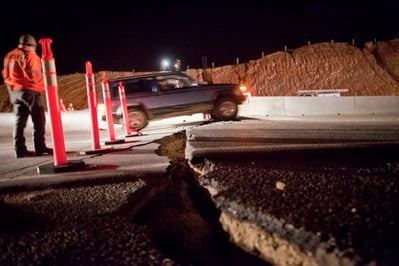A car passes over a crack on the road at the 30th kilometer of the Mexicali-Tijuana highway made by a 7.2 earthquake in Mexicali, Mexico, Sunday, April 4, 2010.  (AP Photo/Guillermo Arias)