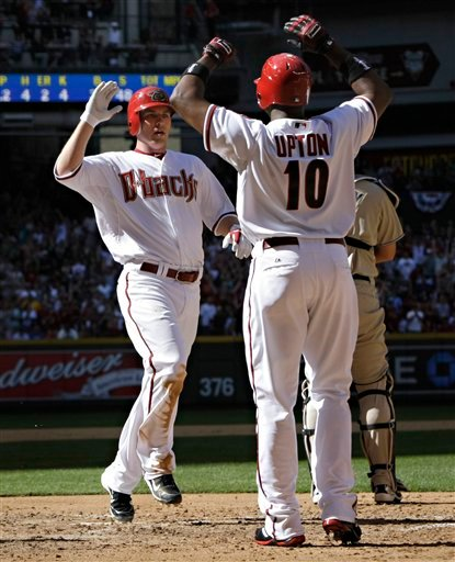 Arizona Diamondbacks' Stephen Drew high-fives teammate Justin Upton (10) after hitting an inside-the-park, two-run home run against the San Diego Padres during the fourth inning of their MLB season opener baseball game Monday, April 5, 2010, in Phoenix.