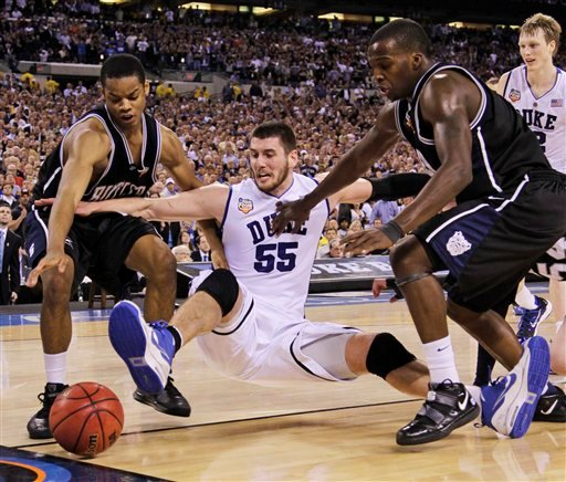 Duke's Brian Zoubek (55) kicks the ball out of bounds between Butler's Ronald Nored, left, and Shelvin Mack in the final minute of play in the men's NCAA Final Four college basketball championship game Monday, April 5, 2010, in Indianapolis.