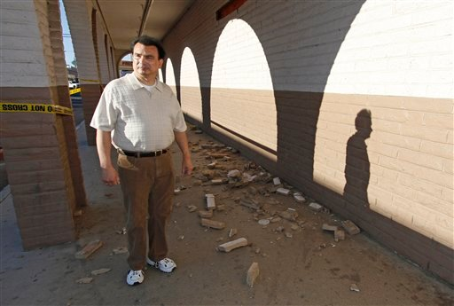 Pharmacy manager Robert Escalante walks past fallen bricks outside his store in downtown Calexico, Calif. Monday, April 5, 2010.  (AP Photo/Denis Poroy)