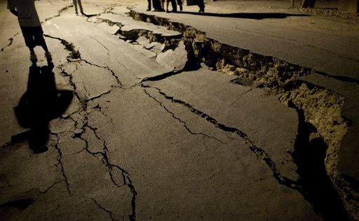 Men stand next to cracks on a street in Mexicali, Mexico, early Monday, April 5, 2010 after Sunday's powerful earthquake. According to the USGS, the earthquake's epicenter was 26 km (16 miles) south west from Guadalupe Victoria, Baja California, Mexico.