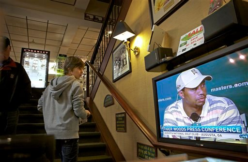 Pierre Simon, 16, of Dunkirk, France, watches the Tiger Woods news conference while shopping at New York Golf Center in New York, Monday, April 5, 2010.