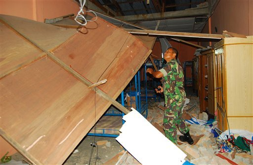An Indonesian soldier inspects the damage at a dormitory for nurses after an earthquake in Subulussalam, Aceh province, Indonesia, Wednesday, April 7, 2010. The magnitude 7.7 earthquake shook Indonesia's northwest island of Sumatra early Wednesday.