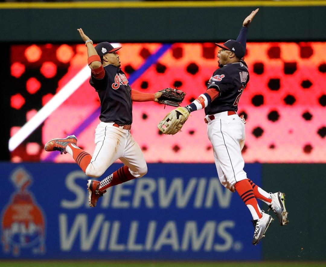 Cleveland Indians' Francisco Lindor and Rajai Davis celebrate after Game 1 of the Major League Baseball World Series against the Chicago Cubs Tuesday, Oct. 25, 2016, in Cleveland. The Indians won 6-0 to take a 1-0 lead in the series. (AP Photo/David J. Ph