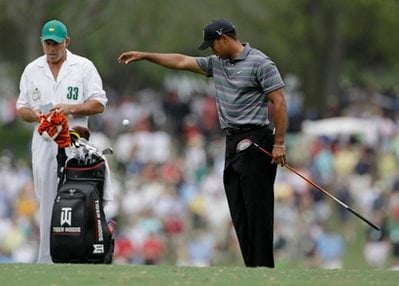 Caddie Steve Williams watches as Tiger Woods takes a drop on the first fairway during the first round of the Masters golf tournament in Augusta, Ga., Thursday, April 8, 2010. (AP Photo/Rob Carr)