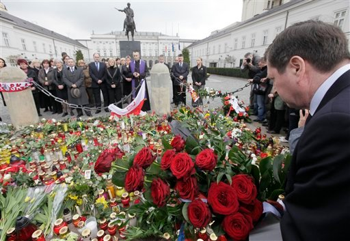 Staff of the Presidential Palace, background, hold a prayer in Warsaw, Poland, Saturday, April 10, 2010, as news broke out about Polish President's Lech Kaczynski death. (AP Photo/Czarek Sokolowski)