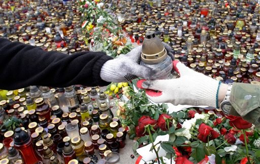 Volunteers hold a candle in front of the Presidential Palace in Warsaw, Poland, Sunday, April 11, 2010, after Polish President Lech Kaczynski died in a plane crash. (AP Photo/Petr David Josek)