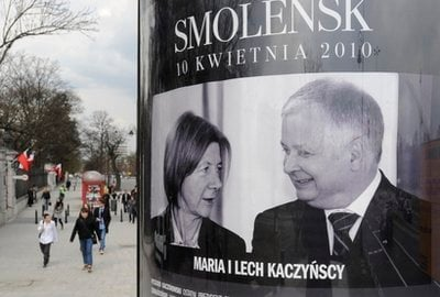 People walk past a poster showing the late Polish President Lech Kaczynski and his wife Maria in downtown Warsaw, Poland, Monday, April 12, 2010.