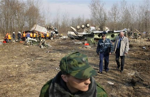 An Interior ministry soldier guards as investigators walk at the site of the Polish presidential plane crash in Smolensk, western Russia, Monday, April 12, 2010.