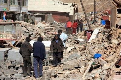 In this photo released by Chiuna's Xinhua News Agency, people walk on the ruins of collapsed buildings after a quake in Yushu County, northwest China's Qinghai Province, Wednesday, April 14, 2010.
