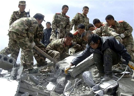 In this photo taken Wednesday, April 14, 2010, rescuers search for survivors in the ruins after an earthquake at Jiegu township in Yushu county, western China's Qinghai province.