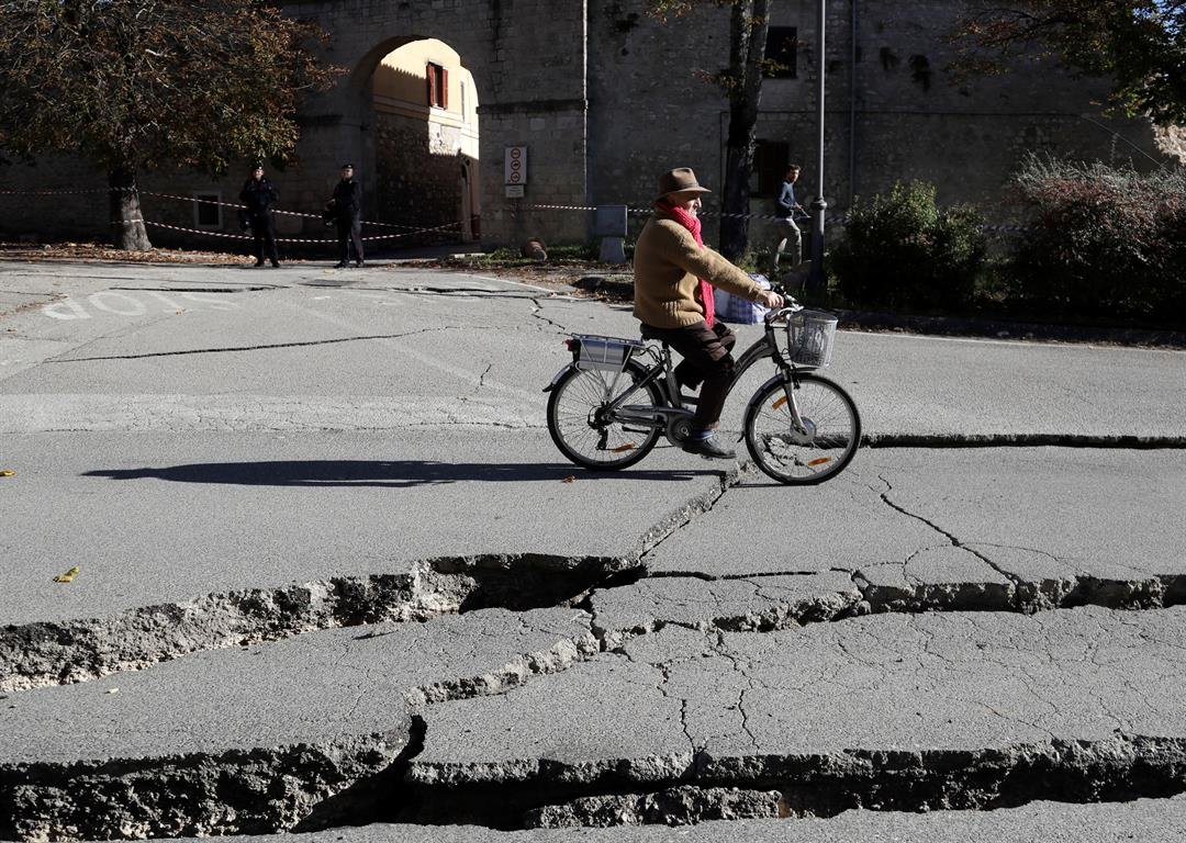 A man rides a bicycle past cracks in a road in Norcia, central Italy, after an earthquake with a preliminary magnitude of 6.6 struck central Italy, Sunday, Oct. 30, 2016. Central Italy was hit by another powerful earthquake Sunday, toppling buildings that
