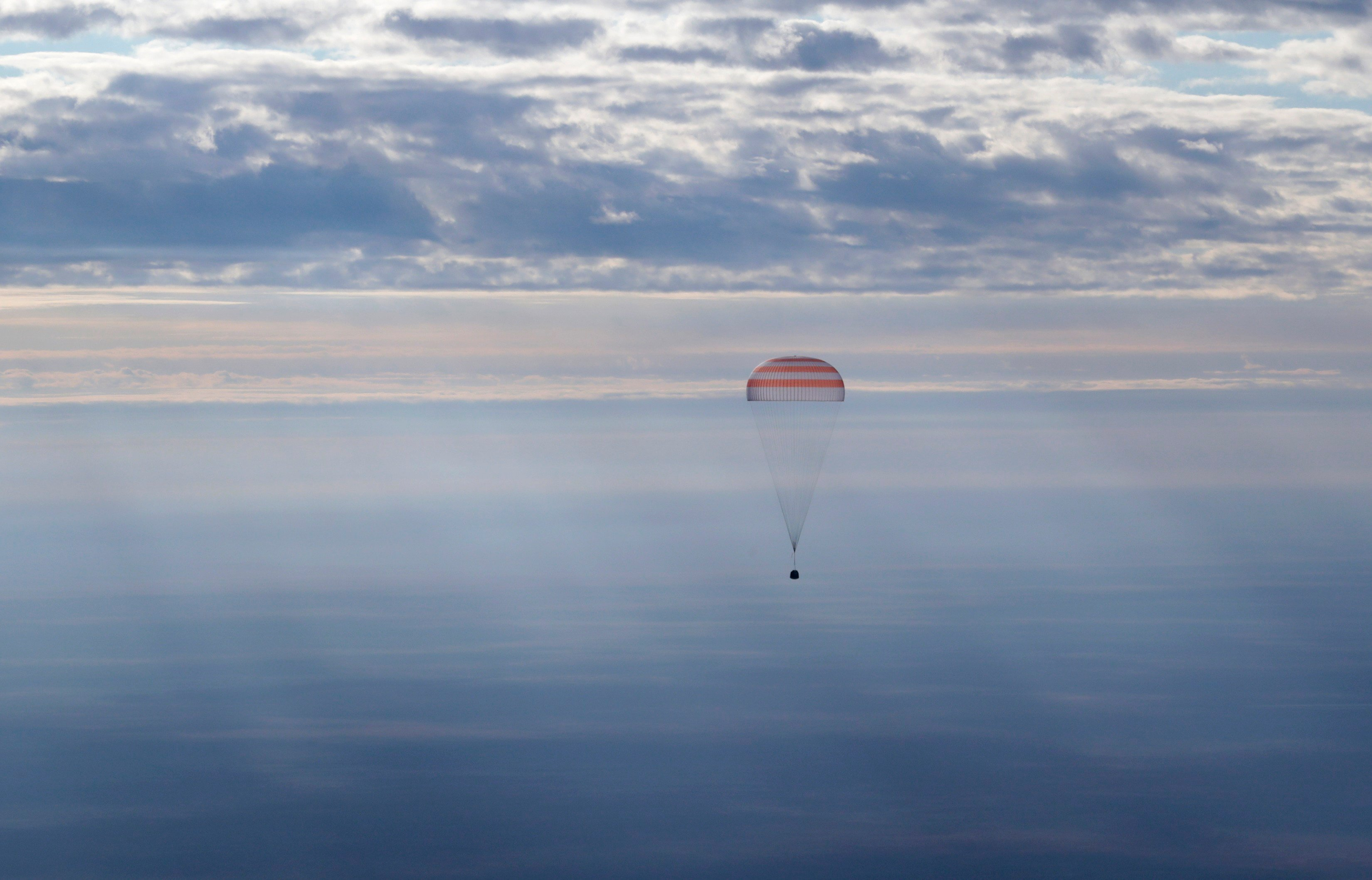 A Russian Soyuz MS space capsule descends about 150 km (90 miles) southeast of the town of Dzhezkazgan, Kazakhstan, Sunday, Oct. 30, 2016. A Soyuz space capsule with U.S. astronaut Kate Rubins, Russian cosmonaut Anatoly Ivanishin, and Japanese astronaut T
