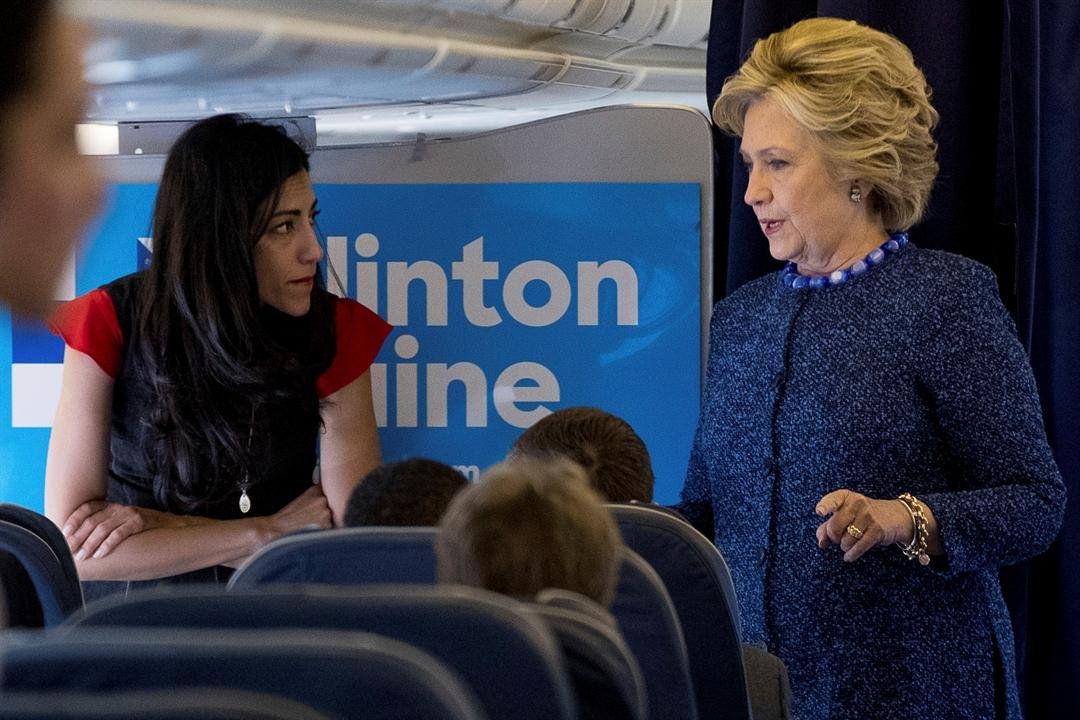 In this Oct. 28, 2016 file photo, Democratic presidential candidate Hillary Clinton speaks with senior aide Huma Abedin aboard her campaign plane at Westchester County Airport in White Plains. The longtime Hillary Clinton aide at the center of a renewed F