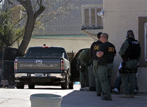 DEA, Immigration and Custom Enforcement agents surround a duplex at the corner of Crawford and West streets in downtown Nogales, Ariz., April 15, 2010 during a large-scale immigration raid. (AP Photo/Nogales International, Manuel C. Coppola)