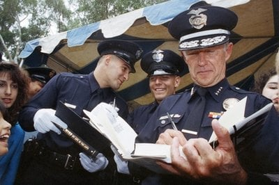 FILE - In this May 29, 1992 file photo, Los Angeles Police Chief Daryl Gates autographs his book for new police officers after their graduation in LA.