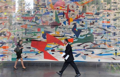 "People walk past Julie Mehretu's ""Mural"" in the lobby of the Goldman Sachs headquarters in the Lower Manhattan area of New York, Friday, April 16, 2010. (AP Photo/Diane Bondareff)"