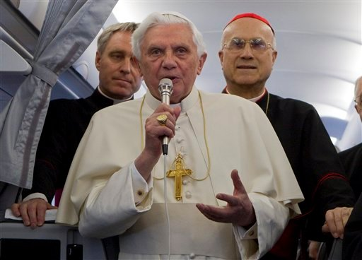 Pope Benedict XVI, flanked by his secretary Georg Gaenswein, left, and Vatican secretary of state Cardinal Tarcisio Bertone, talks to journalist on an aircraft on his way to Malta, Saturday, April 17, 2010. (AP Photo/Andrew Medichini)