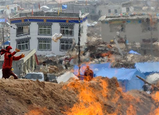 A Tibetan monk throws a cloth used to wrap a corpse during a mass cremation for victims of Wednesday's earthquake in Yushu County, west China's Qinghai province, Saturday, April 17, 2010.  (AP Photo)
