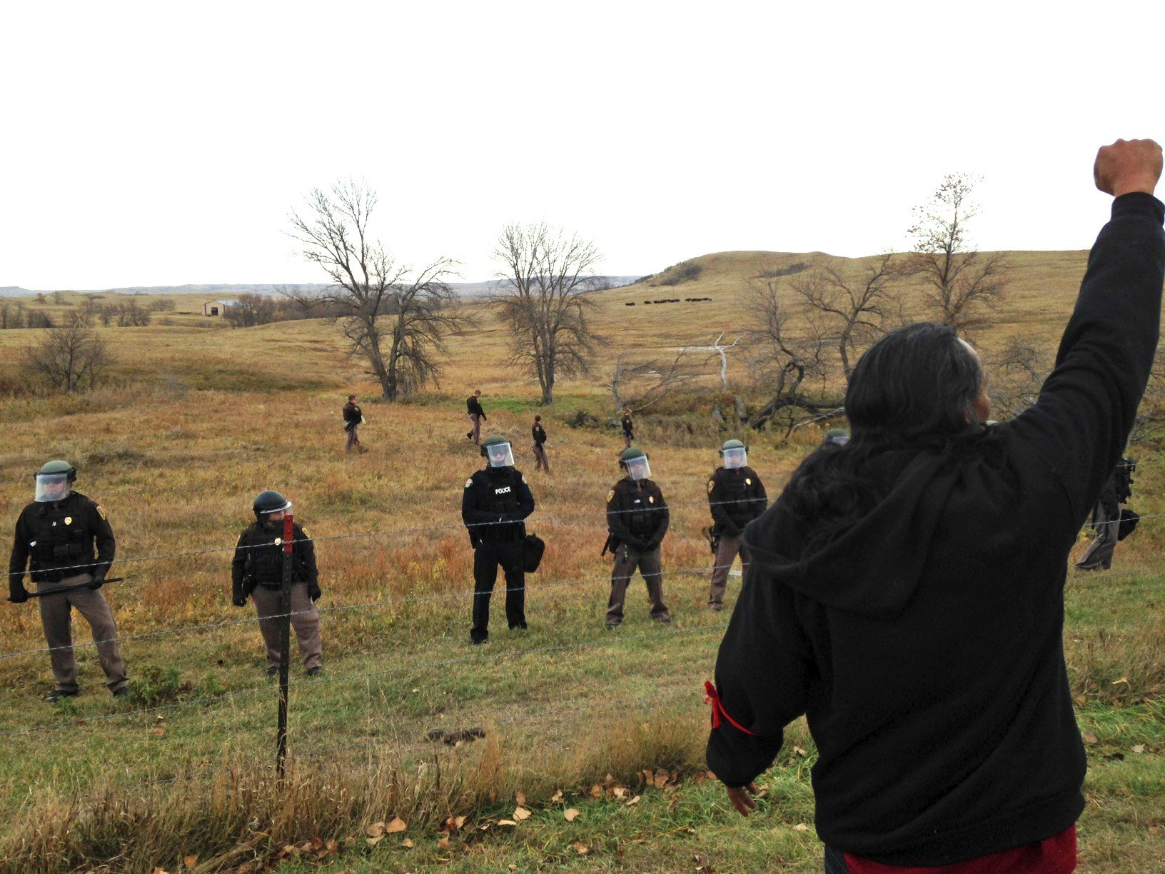 A Dakota Access pipeline protester defies law enforcement officers who are trying to force them from a camp on private land in the path of pipeline construction, Thursday, Oct. 27, 2016 near Cannon Ball, N.D. Soldiers and law enforcement officers dressed