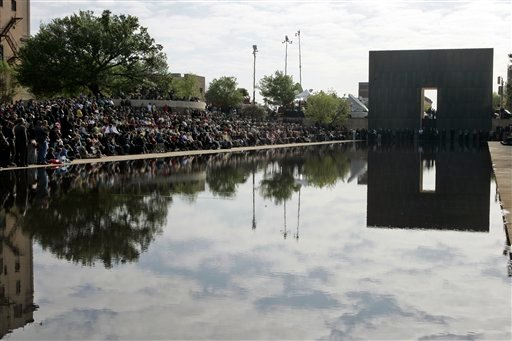 People gather under the Survivor Tree at the Oklahoma City National Memorial, Monday, April 19, 2010, during the memorial ceremony marking the 15th anniversary of the Oklahoma City bombing. (AP Photo/Sue Ogrocki)