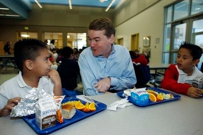 U.S. Sen. Michael Bennet, D-Colo., center, shares lunch with 7-year-old Sigifredo Orona, left, and 8-year-old Michael Zamarano during an appearance at Coronado Hills Elementary School in the north Denver suburb of Thornton, Colo.