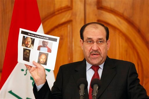 Iraq's Prime Minister Nouri al-Maliki holds a paper displaying photographs of a man the Iraqi government claims to be al-Qaida leader Abu Omar al-Baghdadi at a news conference in Baghdad, Iraq, Monday, April 19, 2010. (AP Photo/Hadi Mizban)