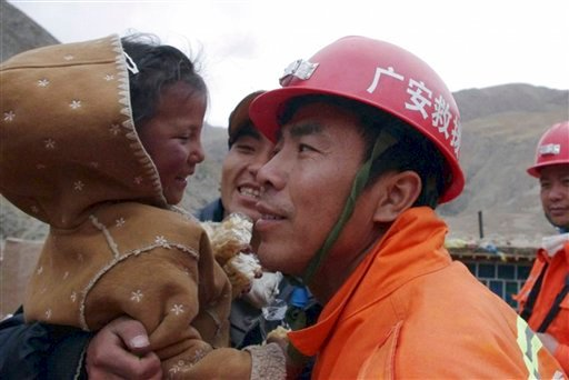 Four-year-old girl Cairen Baji is carried by a rescue worker after they dug her and an elderly woman out from a collapsed mud house near Jiegu town in earthquake-hit Yushu county in west China's Qinghai province on Monday, April 19, 2010.  (AP Photo)