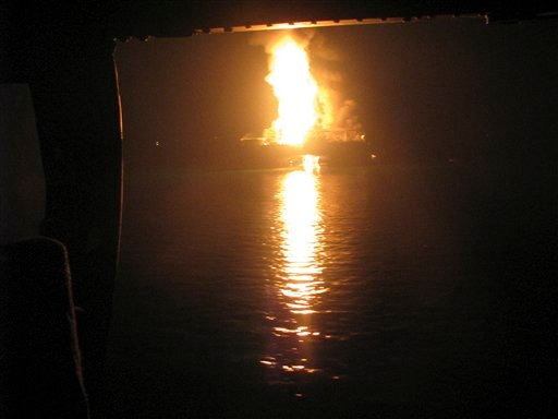 In this Wednesday April 21, 2010 photo released by the U.S. Coast Guard, a fire aboard the mobile offshore drilling unit Deepwater Horizon burns 52-miles southeast of Venice, La. Helicopters.